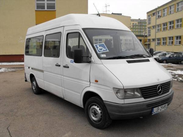 biały bus na parkingu